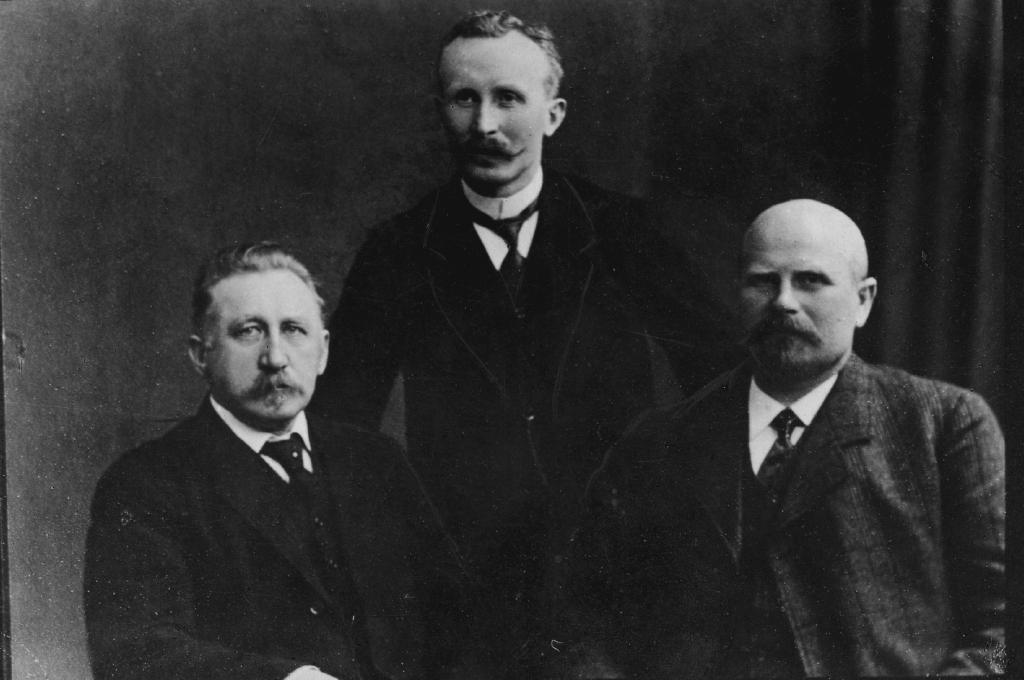 Rigsdagsmand H.P. Hanssen (tv) og landdagsmændene Nis Nissen (stående) og H.D. Kloppenborg-Skrumsager (th)