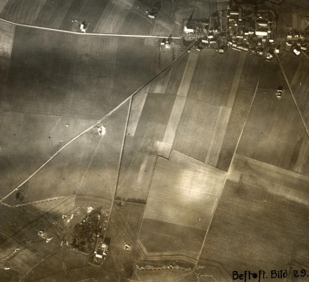 """Luftfoto af Bevtoft 1916/1917. Ejendommen """"Teglgård"""" ses i billedets nederste venstre hjørne. Forløbet af skyttegravstrachéet med slange- og zigzag-formede forbindelsesgrave ses tydeligt. Pigtrådsbælterne ses som to parallelle mørke skygger foran skyttegraven. De fem synlige bunkere på billedet ses som mørke firkanter med hvidt omkring (Johannes Bruchhof, Koblenz)."""