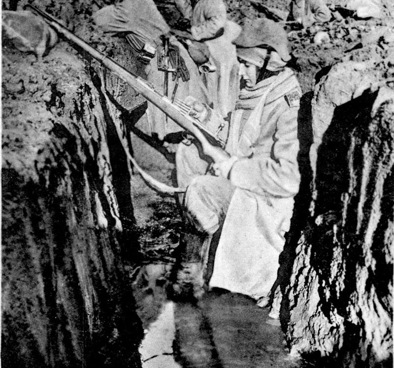 "Udsnit af postkort med soldat i en vandfyldt skyttegrav, under billedet har Thyge Thygesen skrevet ""naturtro stilling"" (Historisk Arkiv for Haderslev Kommune)"